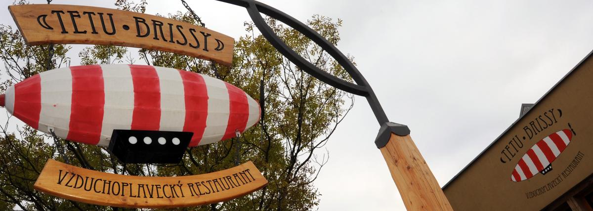Také jsme navrhli a realizovali venkovní aplikace - sloup se svítící vzducholodí a loga na štítu této restaurace.
